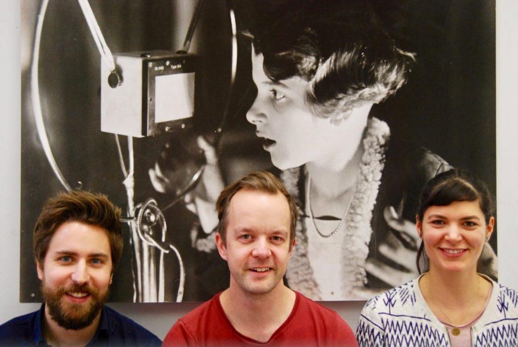 Vor einem Bild mit einem Mädchen mit Mikrofon sitzen die drei PodcasterInnen des museumbug: Matthias, Jörg und Martha