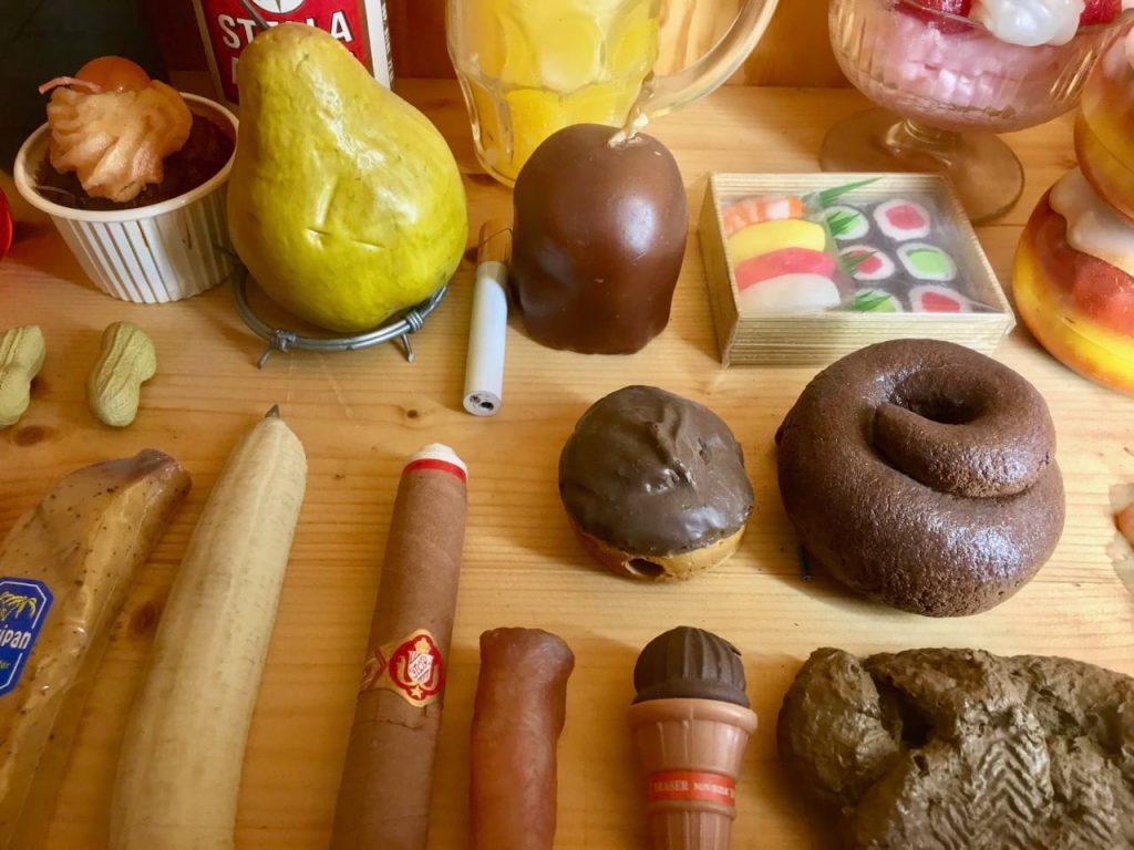 Einige Attrappen aus Plastik im Museum der Dinge. Unter anderem eine Banane, eine Birne, eine Zigarette und ein Haufen Scheisse.