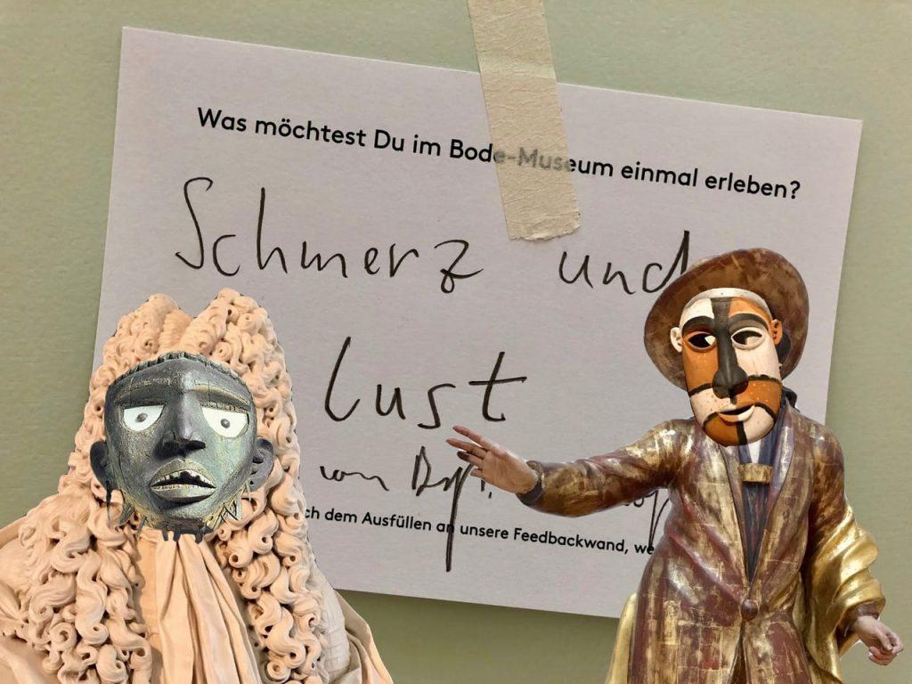 """Im Bildhintergrund eine Feedback-Karte des Bode-Museum. Darauf hat ein Besucher geschrieben """"Schmerz und Lust"""". Im Vordergrund zwei Fotomontagen: Zwei europäische Skulpturen mit den Gesichtern afrikanischer Skulpturen."""