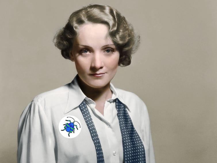 Deutsche Kinemathek. Das kolorierte Foto zeigt Marlene Dietrich, vermutlich in den 1940er Jahre. Sie schaut freundlich in die Kamera. Sie trägt eine weiße Bluse und eine blau-weiss gepunktete, ungebundene Krawatte um den Hals. Auf der Bluse prangt ein Button mit dem Logo des museumbug-Podcast.