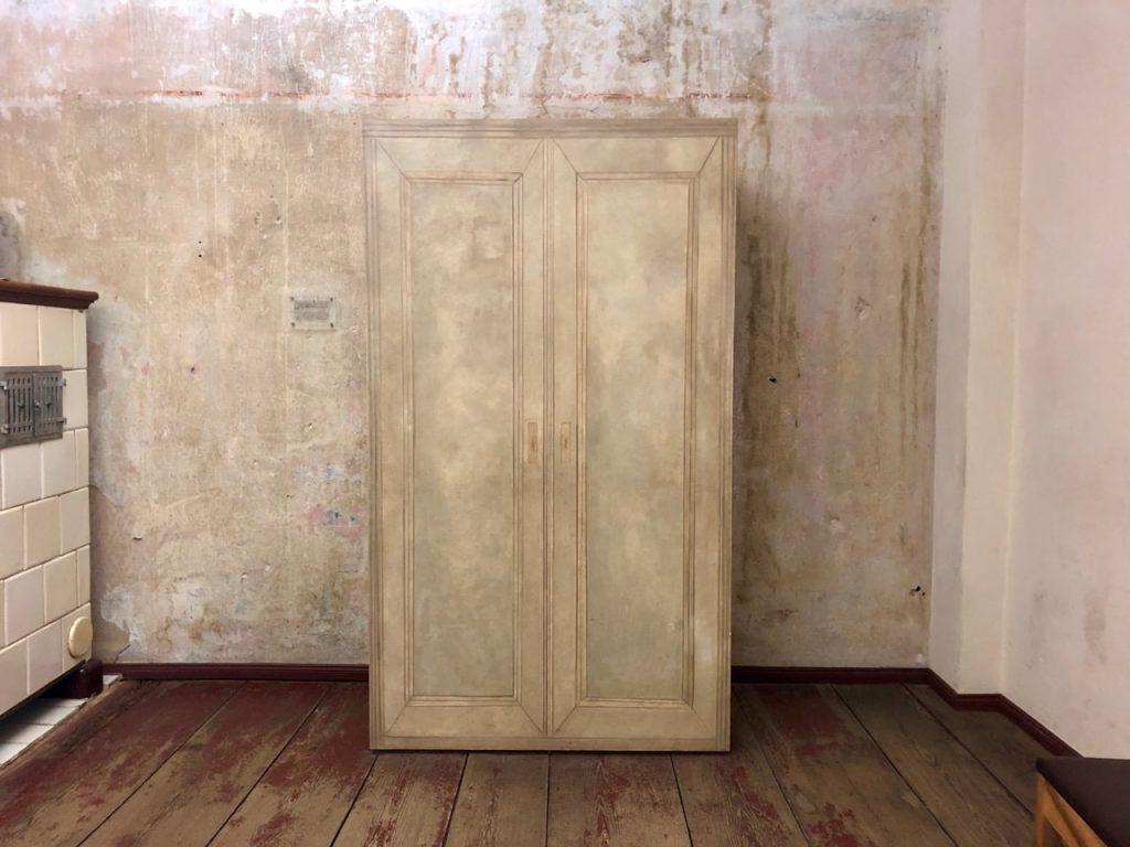 Das Foto zur Folge 5 des museumbug Podcast: Ein Raum mit braunen Holzdielen, einem Schrank und einem Ofen mit hellen Kacheln. Die Wände des Raumes sind unverputzt.