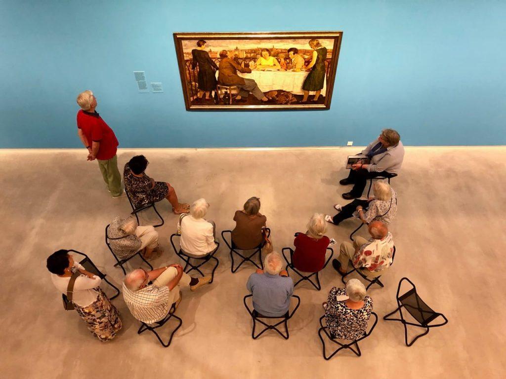 Das Foto zur Folge 6 des museumbug-Podcast. Die Berlinische Galerie. Von schräg oben sieht man eine Gruppe älterer Leute auf Klapphockern sitzen. Sie betrachten ein Bild an einer blauen Wand.