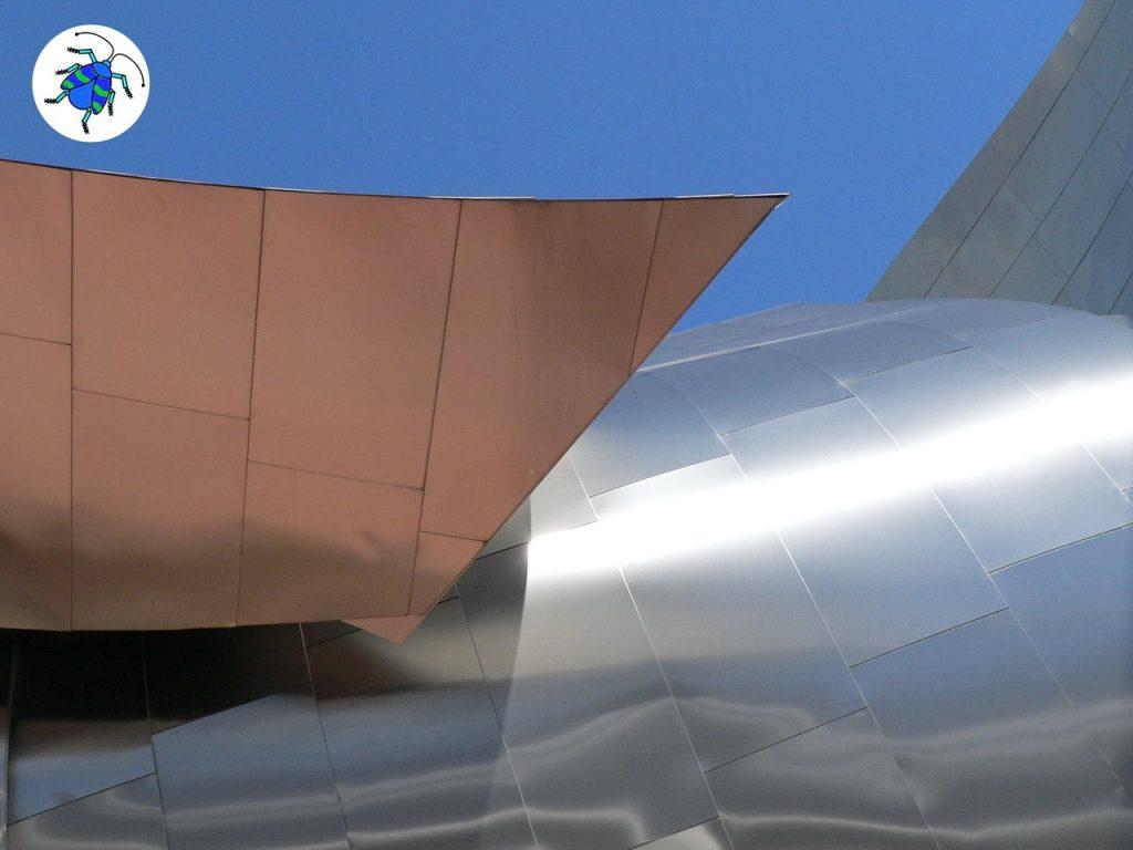 Das Foto zur 10. Folge des museumbug Podcast zeigt das geschwungene Metalldach des Marta Herford. Das Sonnenlicht spiegelt sich darin. Rechts oben steht das museumbug-Logo