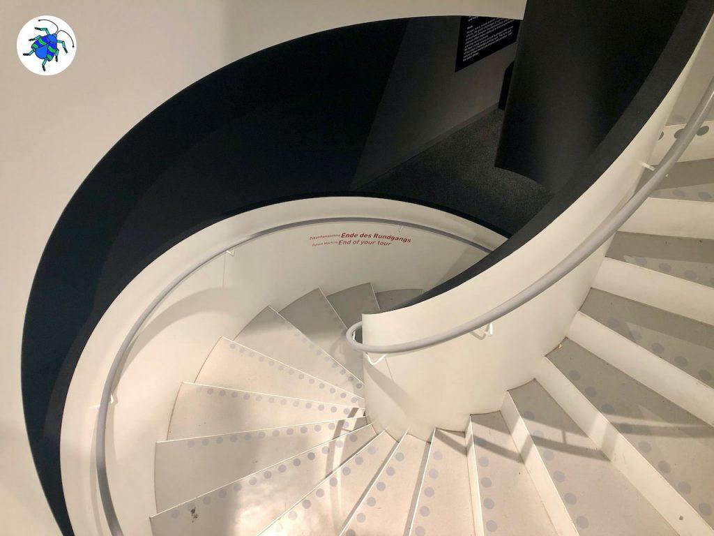 Das Episodenfoto zur elften Folge des museumbug Podcast zeigt den Blick hinunter auf eine Wendeltreppe im Futurium. Die Treppe erinnert mit ihren geschwungenen Formen an ein Schneckengehäuse. Links oben im Bild ist das museumbug-Zeichen zu sehen: EIn blauer Käfer auf weißem Grund.