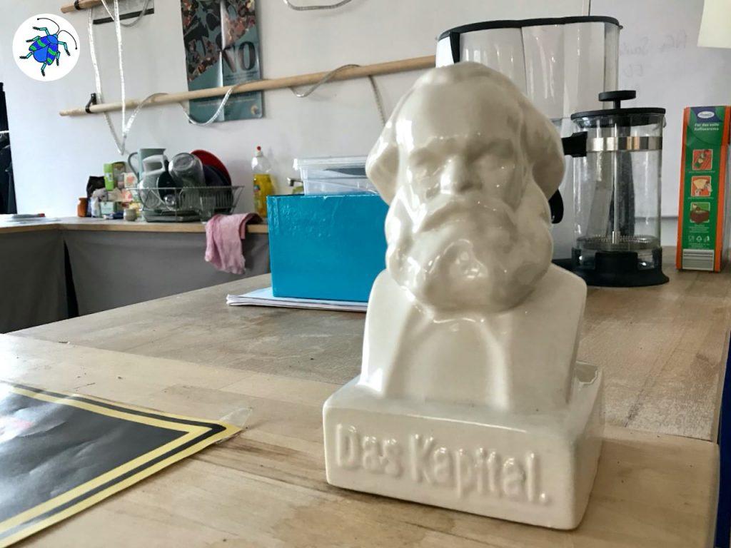 Das Episodenfoto der 12. Ausgabe des museumbug-Podcast zeigt die Anrichte der Küche des Museum des Kapitalismus. Darauf befindet sich eine Spendendose aus Porzelan in der Form von Karl Marx.