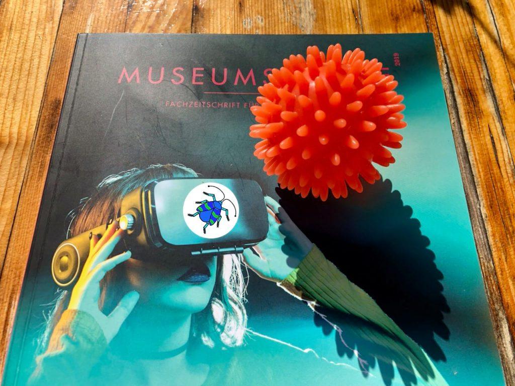 Das Episodenfoto der 13. Ausgabe des museumbug-Podcast zeigt die Fachzeitschrift Museumskunde auf einem Tisch liegen. Auf ihr ist eine junge Frau mit einer VR-Brille abgebildet. Auf der Brille ist das museumbug-Logo zu sehen. Auf der Zeitschrift liegt ein runder, organgener Ball mit Noppen. Er ähnelt dem Corona-Virus.