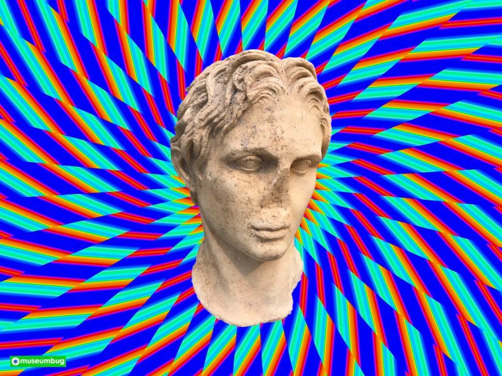 Das Bild zur 15. Folge des museumbug-Podcast. In der Mitte ist der Kopf einer antiken männlichen Statue. Die Augen sind etwas nach unten gerichtet. Die Nase ist abgeschlagen. Der Bildhintergrund besteht aus einer Spirale bunter, psychodelischer Farben