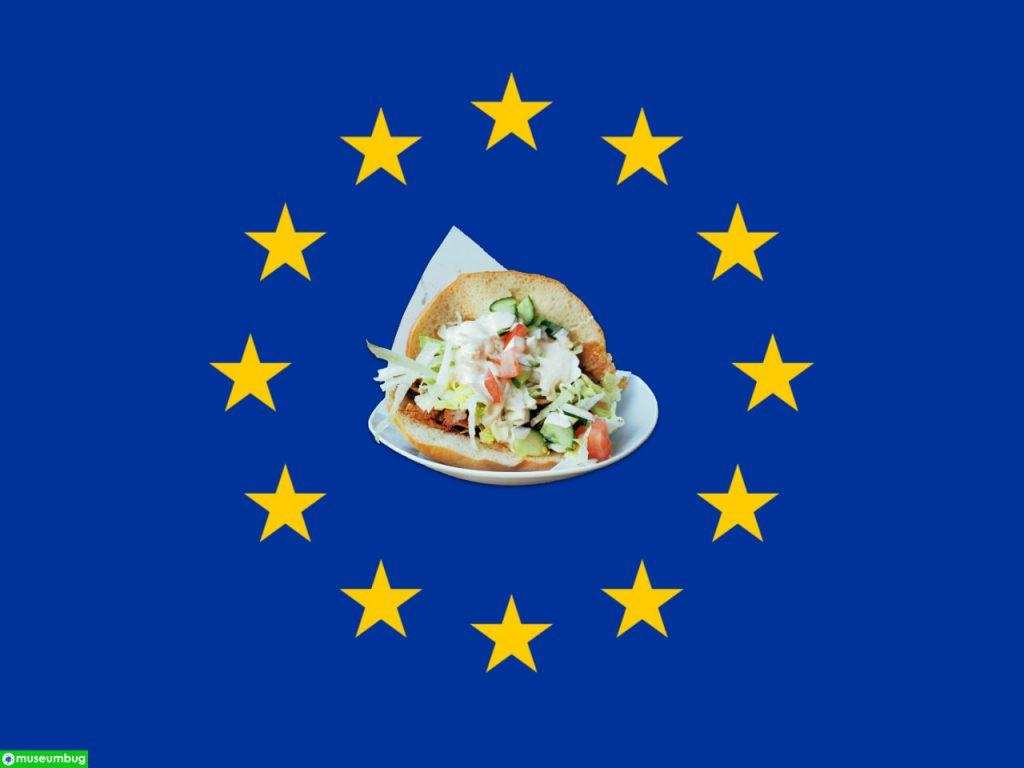 Das Bild zur 17. Folge des museumbug-Podcast zeigt die blaue Flagge der Europäischen Union mit ihre Kreis von zwölft gelben Sternen. In der Mitte befindet sich ein Teller mit einem aufgeklappten Döner.