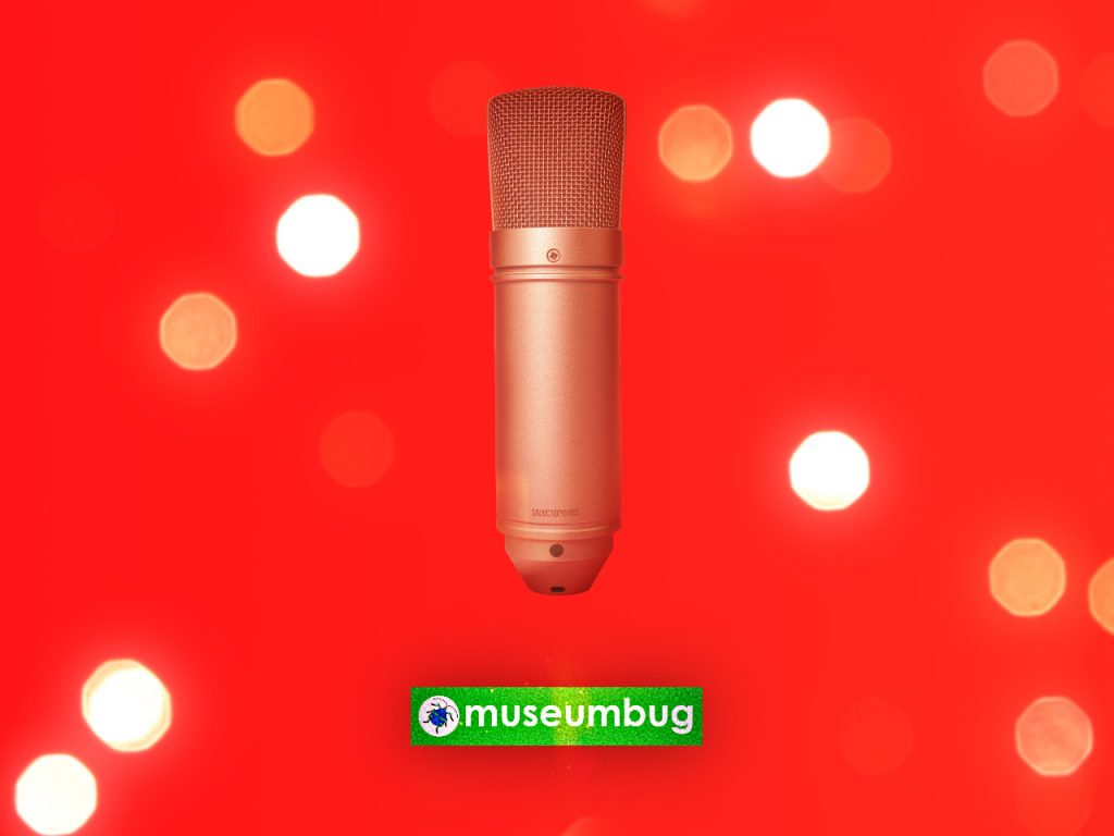 """Das Bild zur Folge 21 des museumbug-Podcast. Es zeigt ein aufrecht stehendes Mikrofon vor einem roten Hintergrund. Drum herum sind weißgelbe Lichtpunkte zu sehen. Am Fuß des Bildes steht der Schriftzug """"museumbug"""" in einem grünen Kasten. Das ganze Bild macht einen weihnachtlichen Eindruck."""