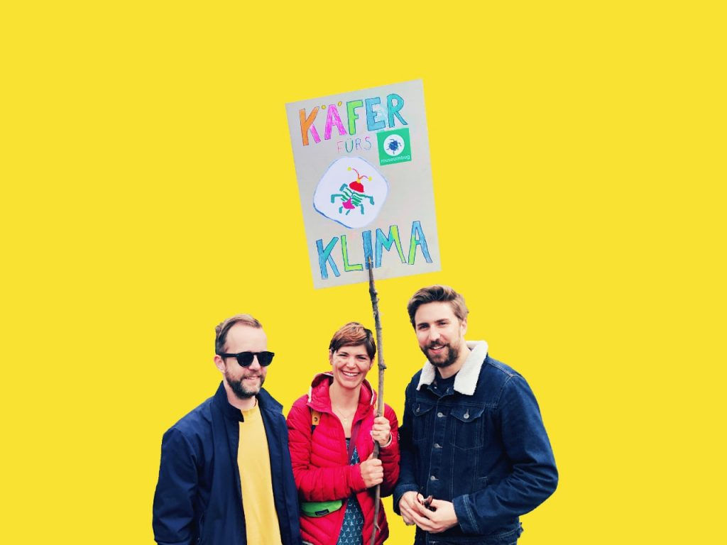 Das Bild der 23. Folge des museumbug-Podcast zeigt Jörg, Martha und Matthias mit einem Demonstrationsschild. Darauf steht: Käfer fürs Klima. Der Hintergrund ist knallgelb.